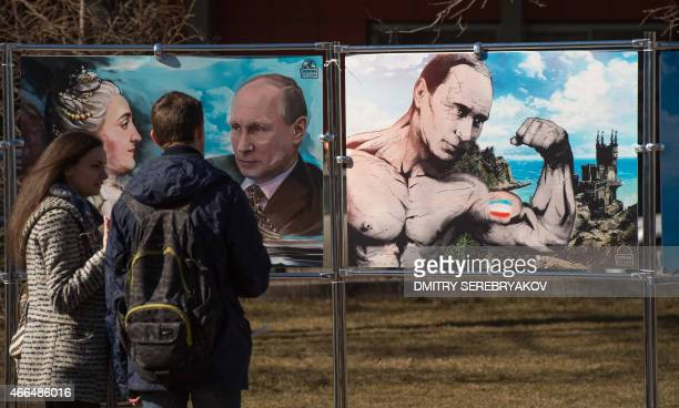 A couple stands by pictures depicting Russia's President Vladimir Putin at an openair political cartoons exhibition dedicated to the oneyear...