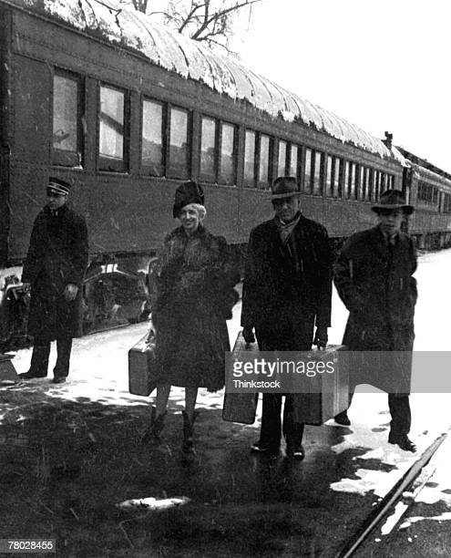 A couple stands holding their luggage as they prepare to travel on a train; the train operator and another man stand behind them in the wintry scene. 1942