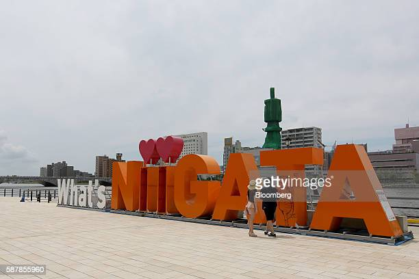 A couple stands in front of a sign along the Shinano River in Niigata Niigata Prefecture Japan on Wednesday Aug 3 2016 In attempting to hit a 2...