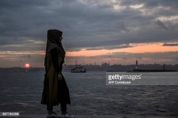 TOPSHOT A couple stands in front of the Bosphorus during sunset on August 22 2017 in Istanbul / AFP PHOTO / BULENT KILIC
