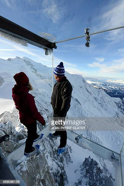 A couple stands in the 'Step into the Void' glass skywalk overlooking the French Alps on top of a 3842metre peak in Chamonix on December 23 2013 The...