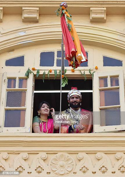 A couple stands near a gudi during Gudi Padwa celebrations at Girgaum on April 8 2016 in Mumbai India Gudi Padwa is the Sanskrit name for Chaitra...