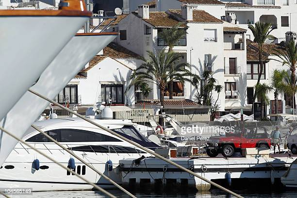 A couple stands next to a jeep parked besides luxury yachts floating in the Puerto Banus harbour on September 29 2010 in Marbella Spain
