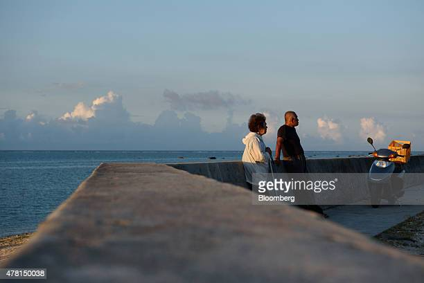 A couple stands on an embankment in Ishigaki Okinawa Prefecture Japan on Saturday June 20 2015 The Abe administration aims to cap increases in...
