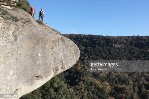 pareja se levanta sobre el precipicio de roca sobre el bosque - flanco de valle fotografías e imágenes de stock