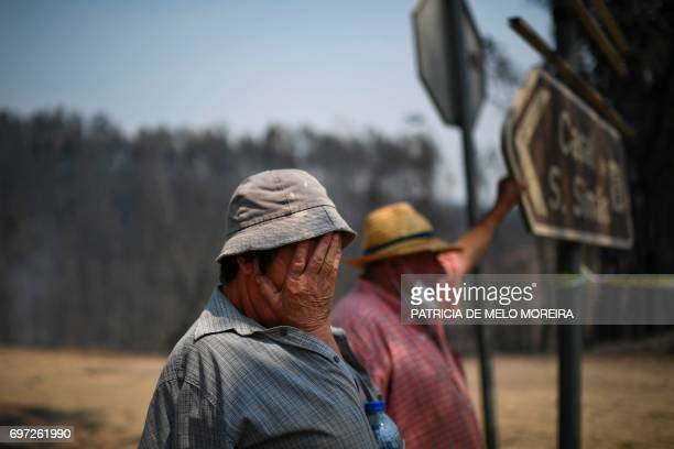 TOPSHOT A couple stands on the roadside watching firefighters passing by in Figueiro dos Vinhos on June 18 2017 Eduardo Abreu 62 years old and...
