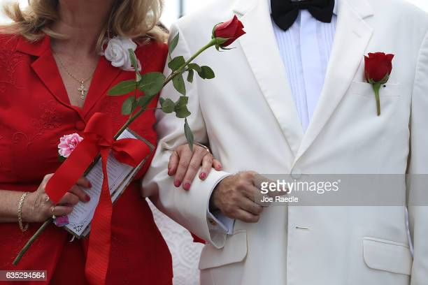 A couple stands together as they participate in a group Valentine's day wedding ceremony at the National Croquet Center on February 14 2017 in West...