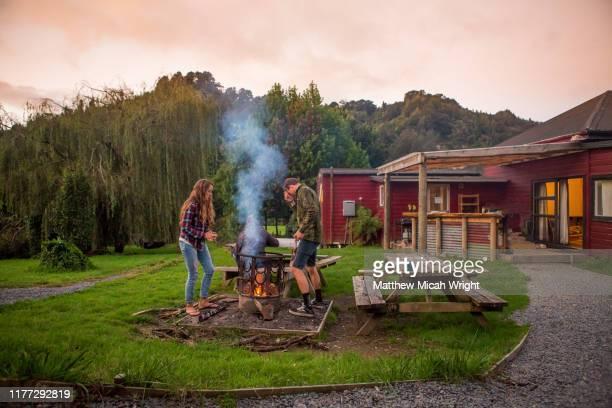 a couple starts a bonfire at the campsite. - ログハウス ストックフォトと画像
