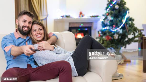couple staying home on new year's eve, watching movies and having fun together, during covid-19 pandemic - 18 23 months stock pictures, royalty-free photos & images