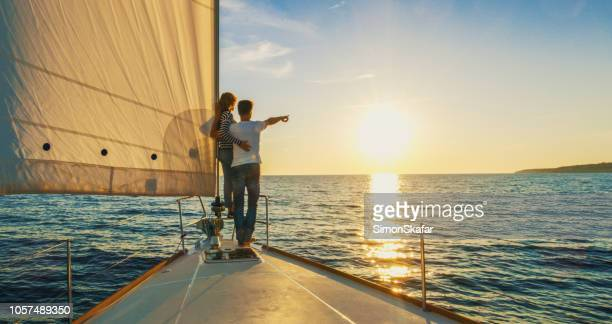 couple staying on edge of prow, croatia - yacht stock pictures, royalty-free photos & images