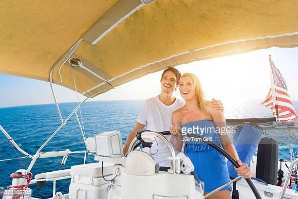 Couple steering boat on ocean