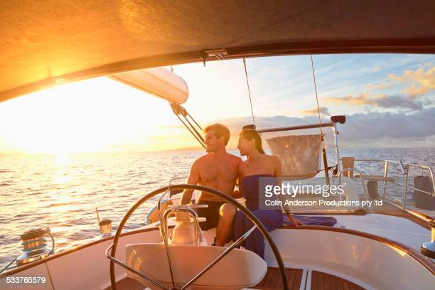 Couple steering yacht together