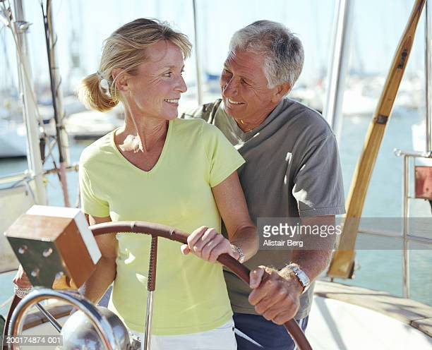 Couple steering yacht wheel, looking at one another, smiling