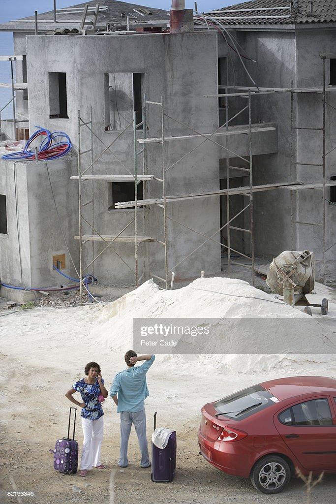 Couple stood by unfinished villa : Stock Photo