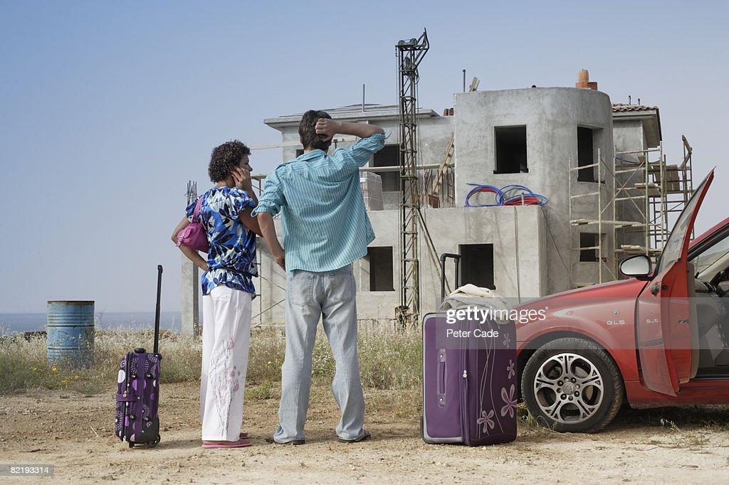 Couple stood in front of half built villa : Stock Photo