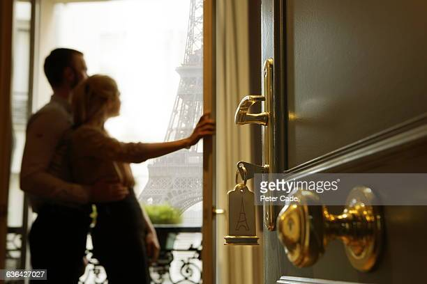 Couple stood on hotel room balcony, Eiffel Tower