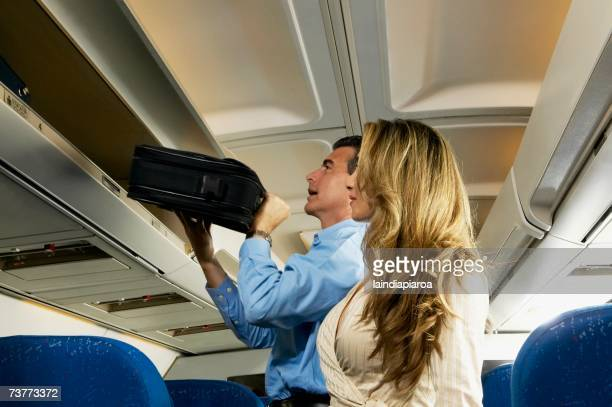 Couple stowing luggage in overhead compartment on airplane