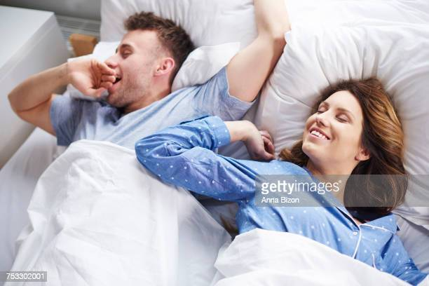 couple stretching and yawning in bed. debica, poland - next to stock pictures, royalty-free photos & images