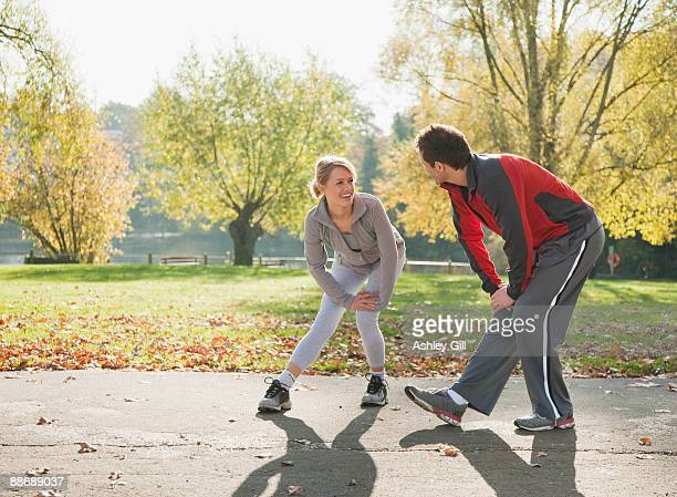 Couple stretching in park in autumn