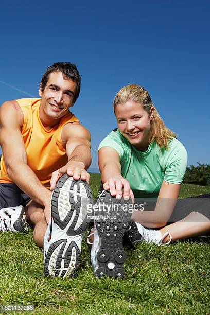 Couple stretching on grass