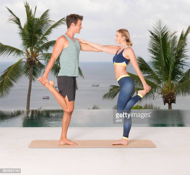 Couple Stretching, Personal Trainer, Fitness Coach motivating his Client on Vacation