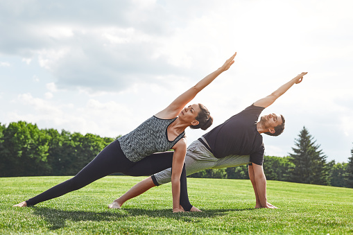 Couple stretching. Young couple stretching and doing yoga exercises in nature on a sunny morning. Healthy lifestyle concept 1139108800