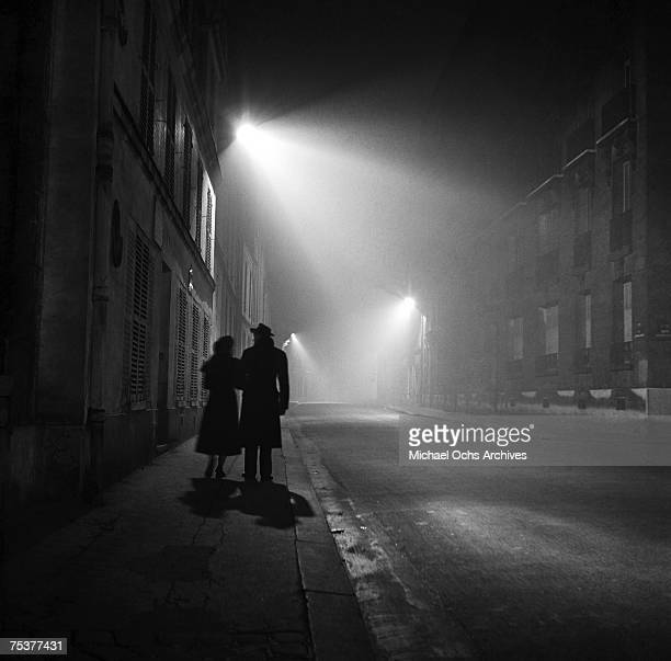 A couple stroll down a foggy street at night on November 1 1948 in Paris France