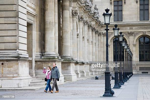 Couple stroll past a row of street lights by The Louvre Museum Paris France