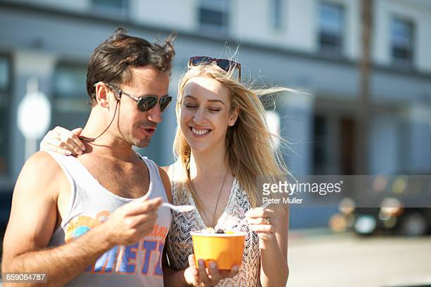 Couple strolling and sharing frozen yoghurt on sidewalk, Venice Beach, California, USA