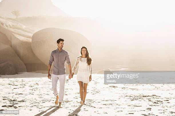 Couple strolling on sunlit beach, Cape Town, South Africa