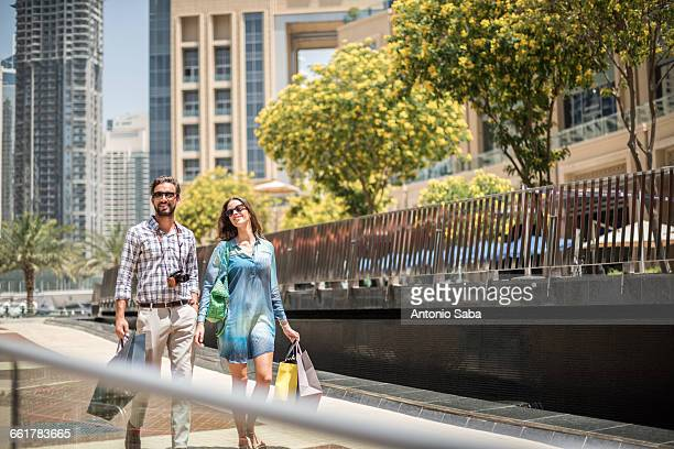 Couple strolling on walkway carrying shopping bags, Dubai, United Arab Emirates