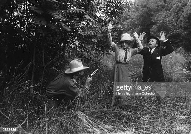 A couple strolling through the woods are surprised by a bandit in a scene from the German gangster film 'Gold or Your Life'
