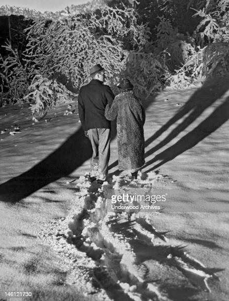 A couple strolls in the moonlight through Rock Creek Park after the heaviest snow fall of the year Washington DC February 17 1937