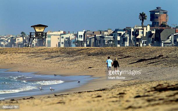 A couple strolls past the houses and shoreline in Sunset Beach where the tight–knit 85–acre seaside community in unincorporated Orange County...
