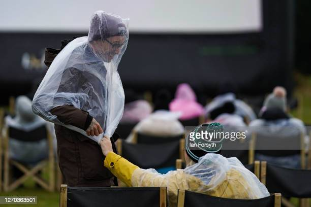 Couple struggle in the wind and rain to put on plastic ponchos as members of the public attend a screening of The Greatest Showman during the Luna...