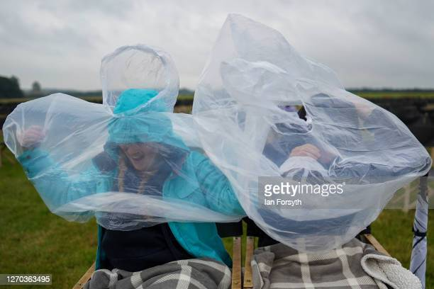 Couple struggle to put on their plastic ponchos during heavy rain as members of the public attend a screening of The Greatest Showman during the Luna...