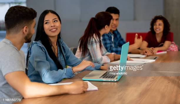 couple student studying together using their laptop while talking at college - hispanolistic stock photos and pictures