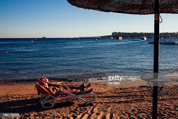 A couple sunbathe at the water's edge at a beach popular with tourists on October 26 2013 in the Red Sea resort town of Sharm El Sheikh Egypt Sharm...