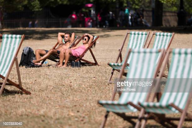 A couple sunbathe on deckchairs in St James's Park in London England during the ongoing summer heatwave on August 07 2018