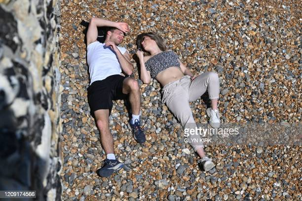 Couple sunbathe on the beach in Brighton, on the south coast of England, on April 5 as the warm weather tests the nationwide lockdown to combat the...