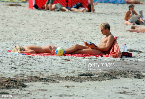 A couple sunbathes at Warnemuende nude beach in Rostock Germany Saturday August 19 2006 As many as 12 million Germans who go to nude beaches at least...