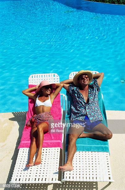 Couple Sunbathing by Pool
