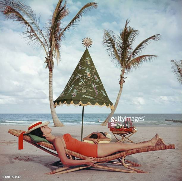 Couple sunbathing by the sea at Palm Beach, Florida, circa 1955.