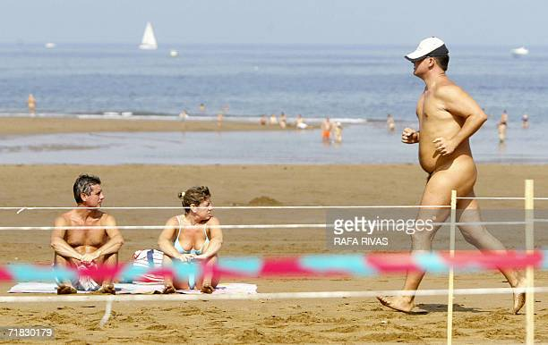 A couple sunbaths as a naked runner takes part in the 'Patxi Ros' nudist crosscountry race 09 September 2006 in the northern Spanish Basque village...