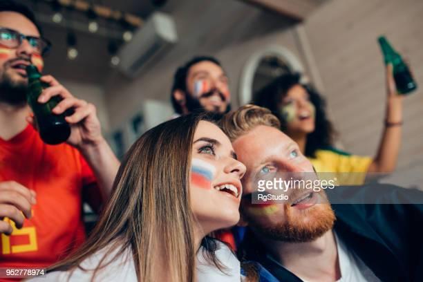 paar, die unterstützung von deutschen und russischen fußball mannschaften beobachten spiel mit freunden - weltmeisterschaft stock-fotos und bilder
