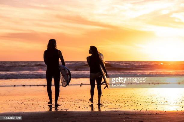 couple surfing in california - venice beach stock pictures, royalty-free photos & images