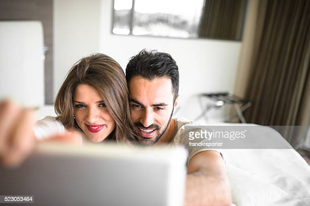couple surfing sitting on the bed doing a selfie