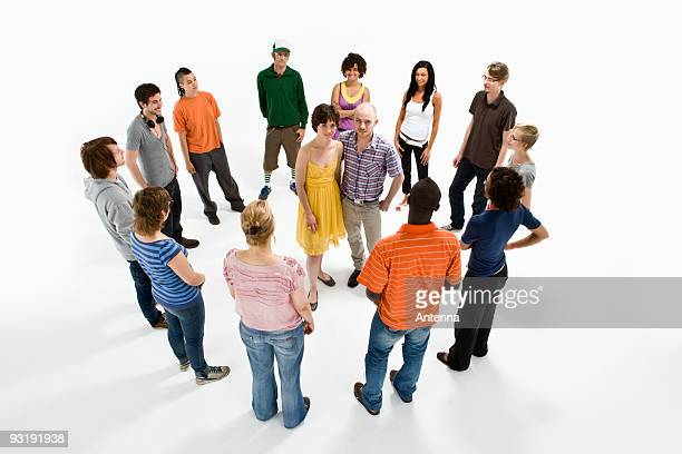 a couple surrounded by a group of men and women - surrounding stock pictures, royalty-free photos & images