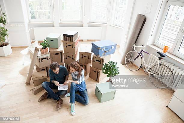 Couple surrounded by cardboard boxes with plan on floor