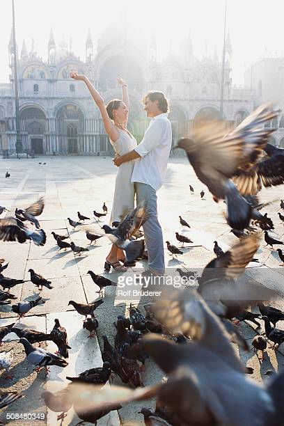 Couple surrounded by pigeons in St. Mark's Square, Venice, Veneto, Italy